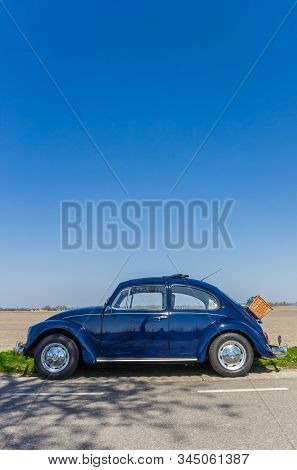 Emmeloord, Netherlands - April 20, 2019: Classic Blue Volkswagen Beetle On A Country Road In The Net