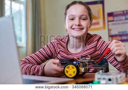Portrait Of Female Pupil Building Robot Car In School Science Lesson