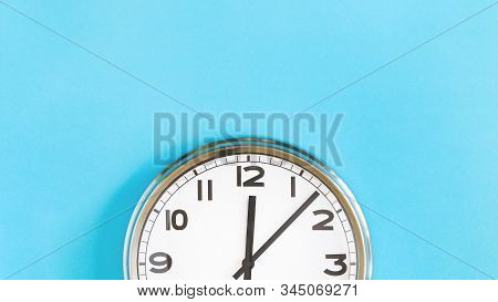 Top Of Big Plain Wall Clock On Pastel Blue Background. Five Past Twelve Oclock. Top View Copy Space,