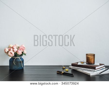Home Office Desk With Copy Space. Pink Flowers, Scented Candle, Stack Of Books On Black Tabetop. Cop