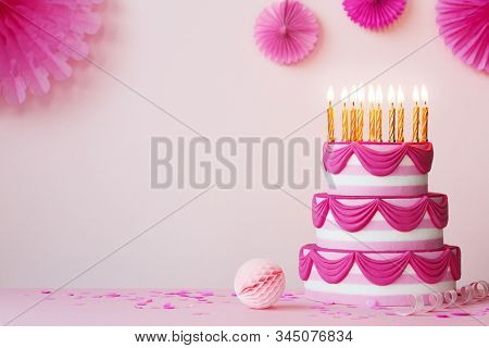 Birthday party with pink tiered birthday cake and golden candles