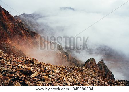 Beautiful Pointy Cliff On High Rocky Mountain Edge Above Precipice With Thick Low Clouds. Atmospheri