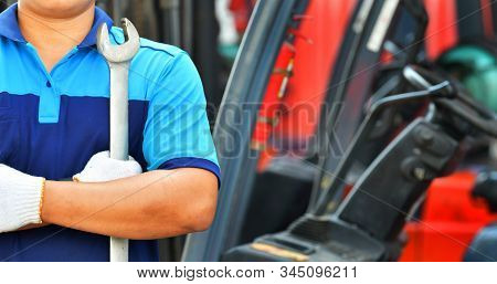 Car Mechanic Wearing A Dark Blue Uniform Stand Holding Wrench On Forklifts Background