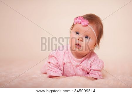 A Cute Little Baby Girl With A Spring Wreath Of Flowers On Her Head Is Very Surprised In The Studio