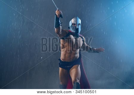 Front View Of Fearless Wet Roman Gladiator In Iron Helmet Attacking With Sword. Muscular Screaming S