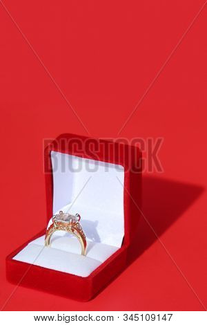 Engagement Ring. Wedding Ring. Gold and Diamond Engagement or Wedding Ring in a Red Velvet Ring Box. Isolated on Red. Room for text. clipping path. Wedding Rings are enjoyed world wide by people.