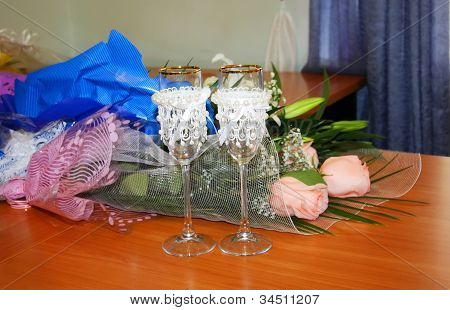 Two Beautiful Decorated Wedding Glasses And Flowers On Table