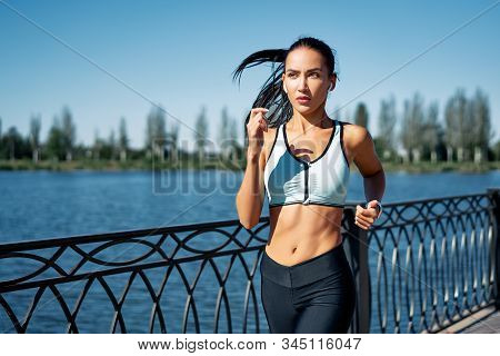 Young Fitness Woman Runner Running At Riverside. Healthy Lifestyle