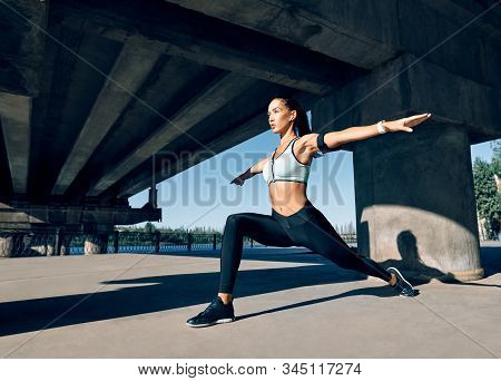 Young Sporty Woman Doing Yoga Asana Warrior I Pose Outdoors Under Industrial Bridge. Practicing Yoga