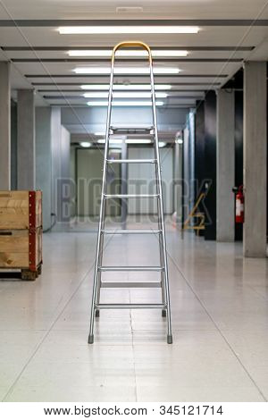 V Shaped Open Ladder Standing On A Laboratory Hallway Corridor Illuminated By Neon Lights Shallow De