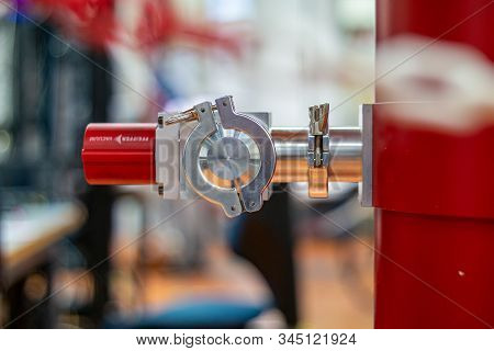 Red Industrial Cylindrical Metal Container With A Bright Aluminum Valve Sticking Out In A Science La