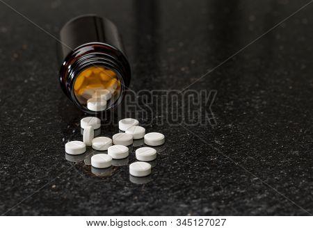 Glass Bottle With White Round Pills. Dark Textured Background