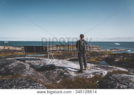 View Towards Icefjord In Ilulissat. Young Man Traveler Tourist Standing On Boardwalk. Icebergs From