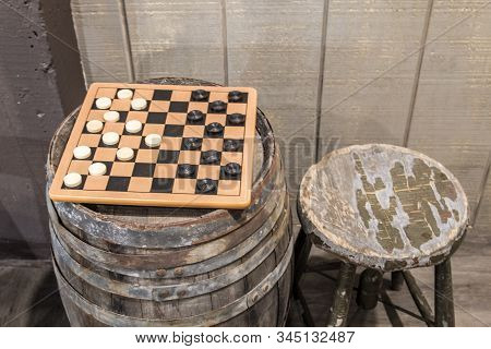 Old Fashioned Game Of Checkers. Checkerboard Game With Checkers On An Old Wooden Keg Barrel With Old