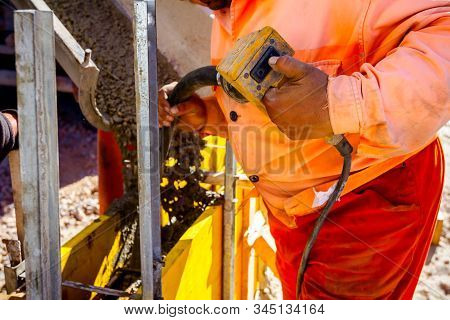 Worker Is Using Power Tool, Compactor, At Concreting Base Of Edifice Wall.
