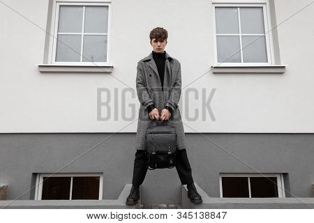 Fashion Model Of A Stylish Young Man In An Elegant Plaid Coat With A Leather Black Vintage Backpack