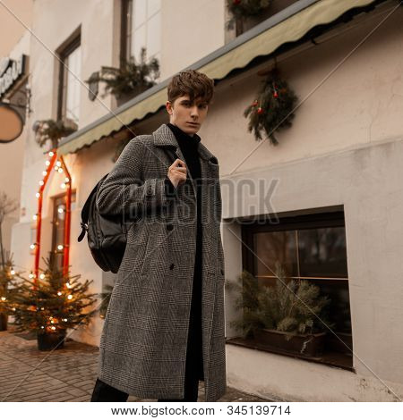 European Young Man In A Trendy Plaid Coat With A Stylish Leather Backpack Walks Along A City Street