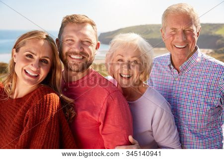 Portrait Of Senior Couple With Adult Offspring On Vacation By The Sea