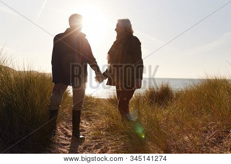 Silhouette Of Loving Senior Couple Holding Hands As They Walk Along Coast Path Against Flaring Sun