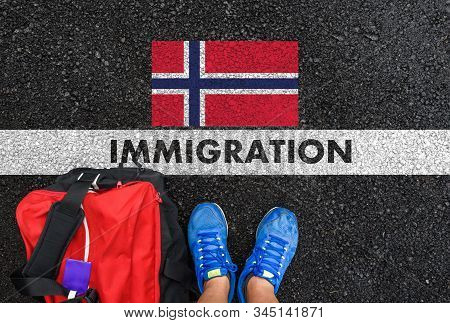 Man In Shoes With Bag Standing Next To Line With Word Immigration And Flag Of Norway On Asphalt Road