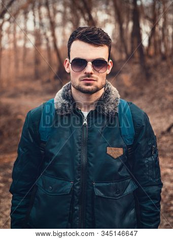 Portrait Of Young Trendy Man In Blue Aviator Bomber Jacket With Sun Glasses Standing On The Path In