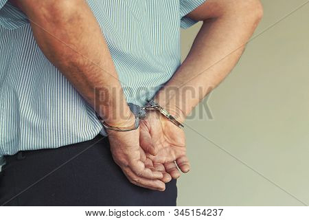 Arrested Man Handcuffed Hands At The Back. Prisoner Or Arrested Terrorist, Close-up Of Hands In Hand