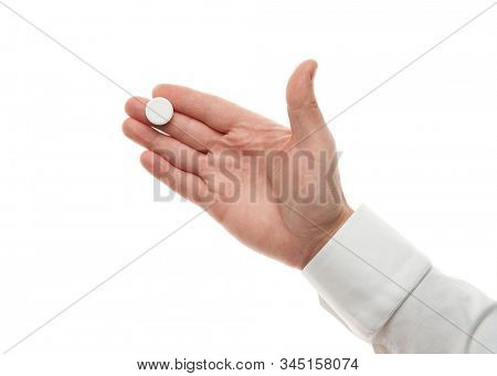 Man hand with one big white pill isolated on white background. White shirt, business style. Medicament and food supplement for health care. Pharmaceutical industry. Pharmacy.