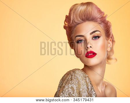 Beautiful woman with creative hairstyle, vivid makeup. Fashionable girl. Beautiful young woman with red lips. Stunning blonde girl. Bright eye makeup. Attractive caucasian model in golden jacket.