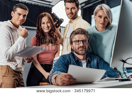 Selective Focus Of Handsome Creative Director And Assistants Looking At Camera In Photo Studio