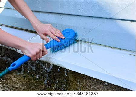 Washing The Facade Of The Building With Water. Clean The Dirty Wall With A Stream Of Water, Brush Of