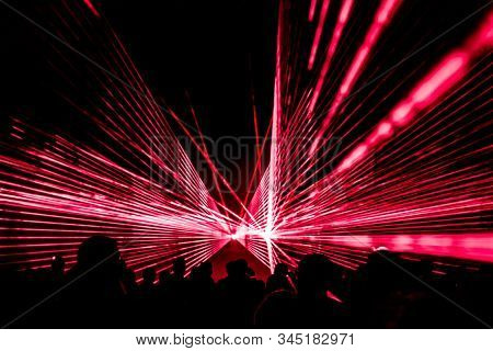 Red Laser Show Nightlife Club Stage With Party People Crowd. Luxury Entertainment With Audience Silh