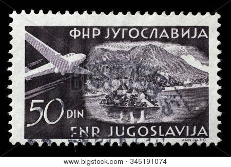 ZAGREB, CROATIA - JUNE 21, 2014: A stamp issued in Yugoslavia shows Lake Bled with islands, Airplanes and Landscapes series, circa 1951.