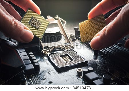 Hands Show Different Processors. Two Cpus Against The Background Of The Motherboard. The Choice Of P