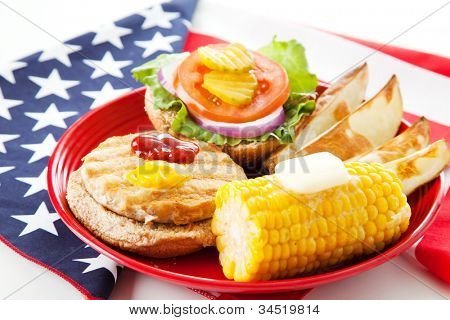 Healthy turkey burger on whole grain bun, with baked potato wedges and corn on the cob. Low fat picnic on an American Flag. Horizontal View