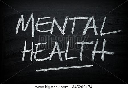 The Words Mental Health Written By Hand On A Blackboard As An Awareness Message