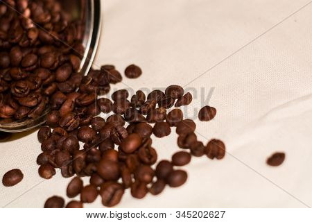 On White Coarse Cloth There Are Grains Of Fresh Arabica Coffee From A Metal Tin Can For Storage.