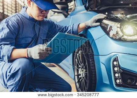 Asian Car Mechanic Technician Holding Clipboard And Checking To Maintenance Vehicle By Customer Clai