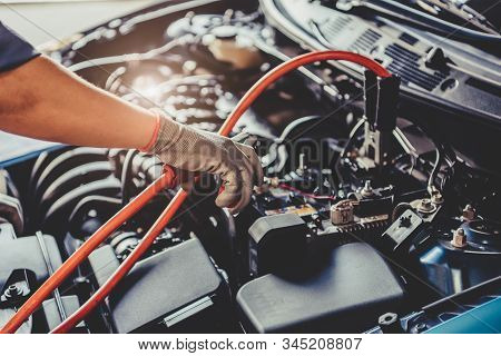 Car Mechanic Holding Battery Electricity Trough Cables Jumper And Checking To Maintenance Vehicle By
