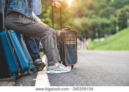 Closeup Lower Body Of Asian Couple Relaxing On Suv Car Trunk With Yellow Trolly Luggage Along Road T