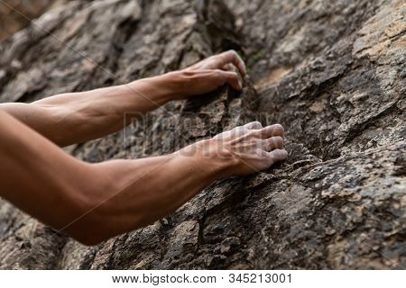 Real Life Struggle Concept As A Man Attempts To Climb A Steep Rock Face. Low Angle View Of Arms Stru