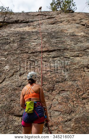 An Advanced Rock Climber Is Seen At The Summit Of A Steep Cliff, Fixing Safety Rope For Beginner Dur