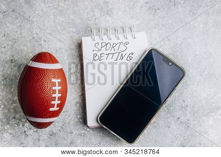 Top View Of Smartphone, Ball And Notepad For Betting Concept. Flat Lay