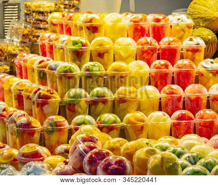 Fresh Fruits And Vegetables Cutted Into Pieces In Plastic Cup, Close Up View. Multicolour Fruits Bac