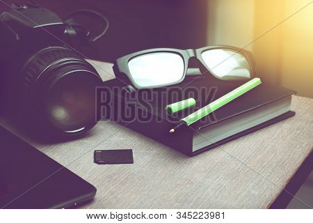 Light Green Pen On Black Notebook Organizer, Smart Phone And Digital Camera With Memory Card On Wood