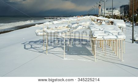 Metal Construction At The Beach Covered With Snow, Unusual Weather On Subtropics