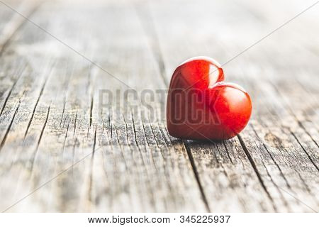 Red heart on old wooden table. Love heart.