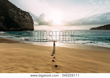 Lonely Man Stands On The Beach Looks Towards The Sun Light. A Man Meets The Sunset On The Beach In I