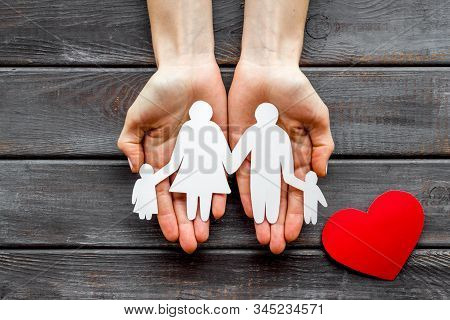 Health Insurance Concept. Family Cutout On Palms Near Heart Icon On Dark Wooden Background Top-down