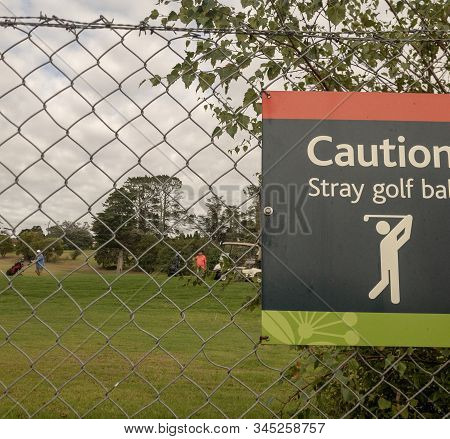 Caution Stray Golf Balls Sign Clipped Onto A Wire Mesh Fence At A Golf Course