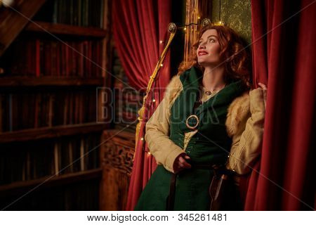 Once upon a time for Christmas, fairy tale. Beautiful young woman with magnificent red hair in a fairytale atmosphere of an old castle decorated for Christmas.